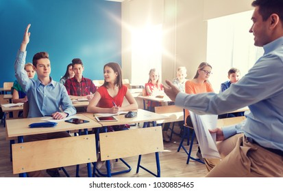 education, school and people concept - group of happy students and teacher with papers or tests