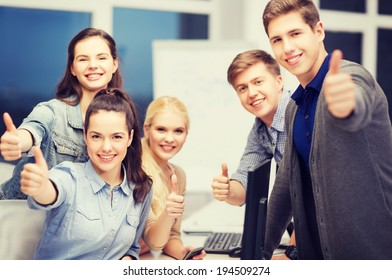 education, school and people concept - students with computer monitor and smartphones showing thumbs up