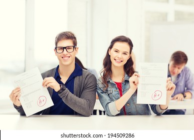 education, school and people concept - two teenagers holding test or exam with grade A