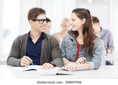 education, school and people concept - two teenagers with notebooks and book looking at each other at school