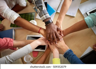 education, school, teamwork and people concept - close up of international students with hands on top of each other sitting at table