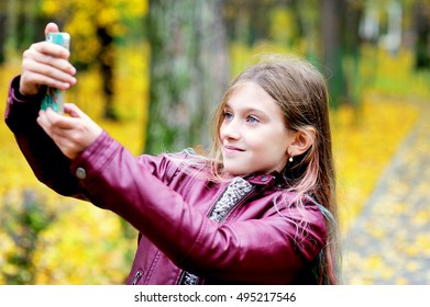 education, school, technology and internet concept - little student girl in uniform with smartphone in the park