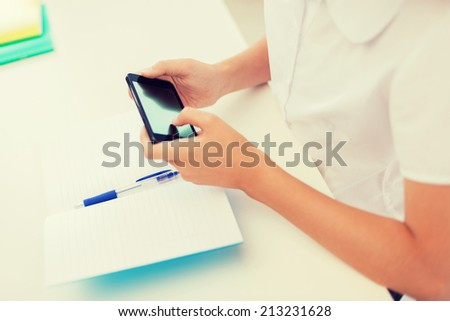 education, school, technology and internet concept - little student girl with notebooks and smartphone at school