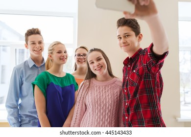 education, school, technology and people concept - group of happy smiling students taking selfie with smartphone