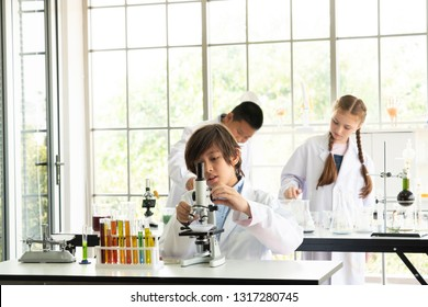 education, science and children concept Attentive school kids doing a chemical experiment with test tubes studying chemistry and microscope in laboratory. Scientific research. at school laboratory - Shutterstock ID 1317280745