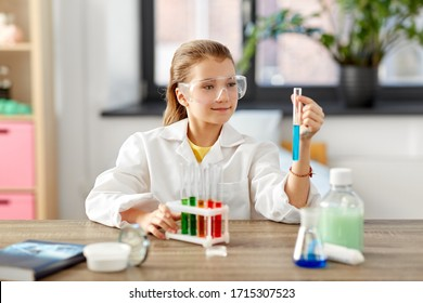 education, science and children concept - girl in goggles with test tube studying chemistry at home laboratory