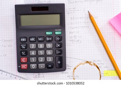 Education and Science concept. Handheld Calculator, Pencil, Ruler over Sheet of Paper with Mathematical Formulas.