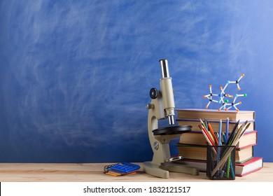Bildungskonzept - Bücher, Molekül-Modell und Mikroskop auf dem Schreibtisch im Auditorium, Chalkboard-Hintergrund.