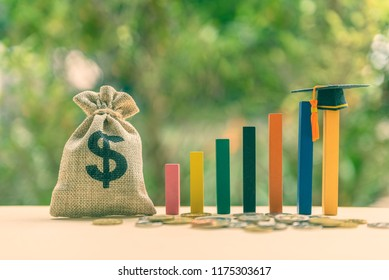 Education or student loan, financial aid and scholarship concept : US dollar cash bag, coins, a black graduation cap or hat / mortarboard on rising wood pole, depict the increasing cost of tuition fee