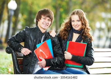 Education and students. Happy young college student with notebooks on bench