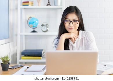 Bildungsstudium im Ausland, asiatische Studentenmädchen mit Brillengläsern schauen auf Laptops, während sie im Ausland Videoanrufe mit Internetfreunden tätigen, verwenden Geschäftsfrauen Computeranalysedaten