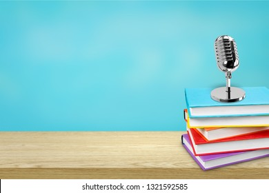 Education teaching concept : Retro microphone with many book put on wooden table isolated on blue background.
