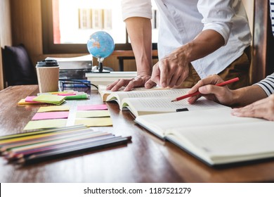 Education, teaching, learning concept. Two high school students or classmates group sitting in library with helps friend doing homework and lesson practice preparing exam to entrance.