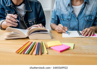 Education, teaching, learning, technology and people concept. Two high school students or classmates with helps friend do homeworks learning in classroom, Tutor books with friends.