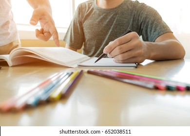 Education, teaching, learning, technology and people concept. Two high school students or classmates with helps friend catching up workbook learning in classroom, Tutor books with friends.