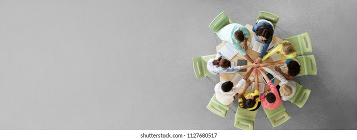 education, teamwork and people concept - group of international students with books and tablet pc computers putting hands on top of each other sitting at round table