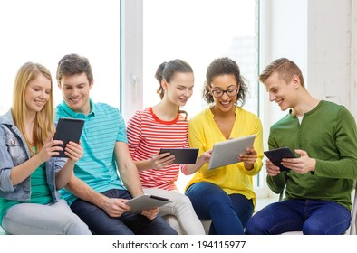 education and technology concept - smiling students with tablet pc computer at school