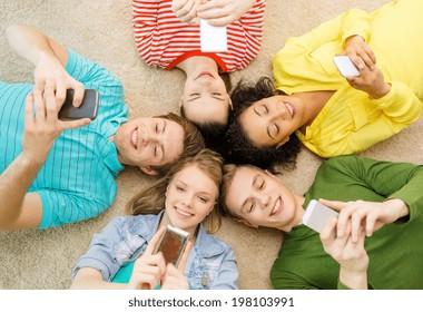 concepto de educación, tecnología y felicidad - grupo de jóvenes sonrientes tendidos en el suelo en círculo con smartphones
