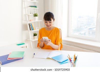 education, technology, learning and people concept - happy asian student girl with book and notebooks using smartphone at home