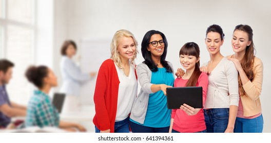 education, technology and people concept - international group of happy smiling different women with tablet pc computer over classroom background