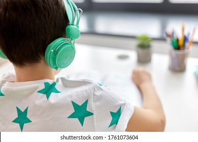 education, technology and school concept - close up of boy in headphones sitting at table at home