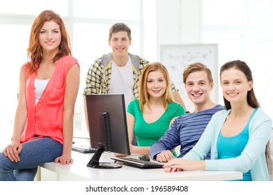 education, technology, school and people concept - group of smiling students having discussion in computer class at school