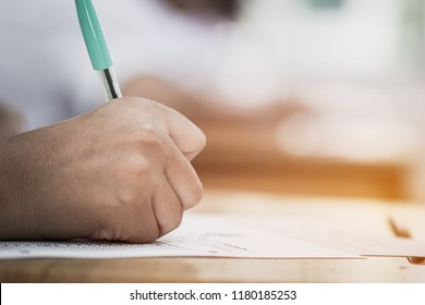Education test concept : Hands with blue pen over application form, Students taking exams, writing examination room with undergraduate inside. Student sitting learning lessons doing final in classroom