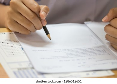 Education test concept : Man Hands high school, university student holding pencil for testing exams writing answer sheet and exercise for taking in exam paper on wood table at classroom with uniforma