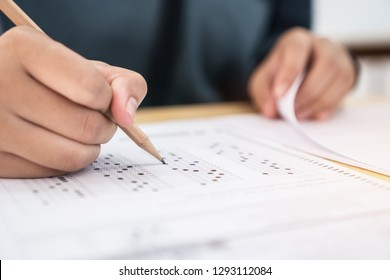 Education test exam concept, high school / university student holding pencil writing paper answer sheet on lecture chair for taking exams in examination room or classroom. Educational assessment ideas