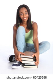 Education time for pretty young African American teenager school girl student with big beautiful smile, sitting on floor wearing blue jeans and vest holding school study books.