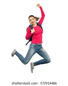 education, travel, tourism, motion and people concept - smiling young woman or student with backpack jumping in air over white background