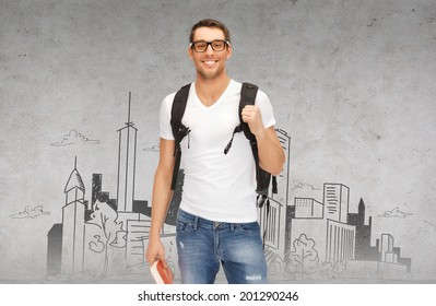 education, travel and vacation concept - smiling student in eyeglasses with backpack and book in front of city sketch
