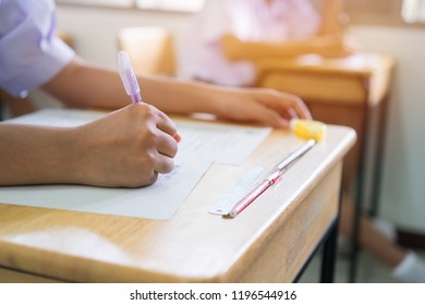 Education uniform students testing exam with pencil for multiple-choice quizzes or testing exams answer sheets exercises in school rows chairs at classroom in Thailand