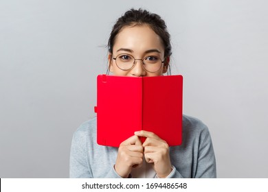 Education, university and people concept. Close-up portrait of romantic young female student, asian girl have secret diary, hiding smile behind planner or notebook, writing notes, grey background