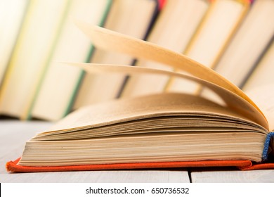 education and wisdom concept - red open book on wooden table