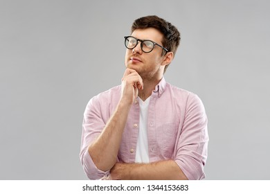 education, wisdom and people concept - thinking young man in glasses over grey background