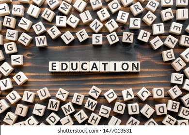 Education - word from wooden blocks with letters, school or college teaching or learning knowledge education  concept, random letters around, top view on wooden background