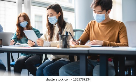 Education And Work During Pandemic. Group of diverse students sitting at table in classroom at high school, wearing surgical face mask, writing test or taking notes in notebook, using digital tablet
