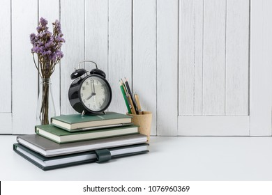 education workspace background concepts Pencil, stationery, flowers, Book, alarm clock White wooden vintage wall. back to school concepts
