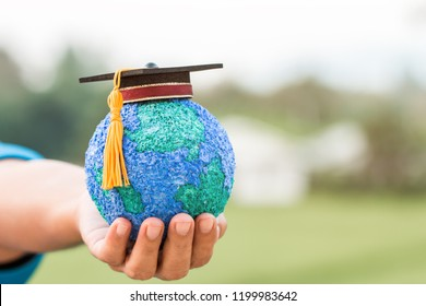 Education world knowledge ideas. Graduation cap on Businessman holding Paper Mache Craft Earth globe in hands. Concept of global business study abroad educational on green blackground, Back to School