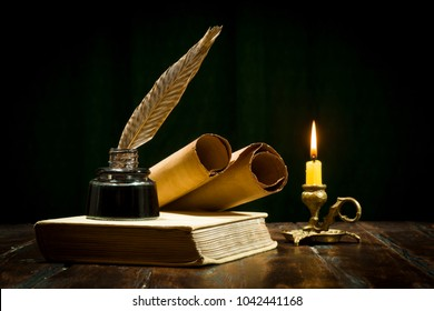 Education and writing concept, pen in ink bottle and candlestick with candle on wooden table on dark background.