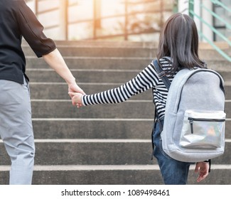 Educational back to school or bring kid to work concept with elementary student girl carrying backpack holding parent woman or mother's hand walking up school admission office building going to class