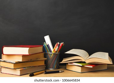 Educational background. Books piles and pencils against empty classroom blackboard for copy space. Back to school concept