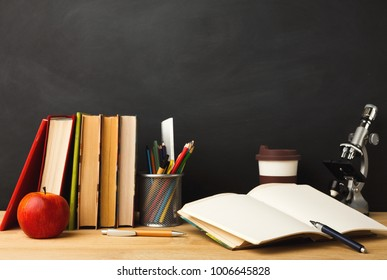 Educational background. Microscope, books, pencils, apple, take away coffee cup and open notebook against empty classroom blackboard for copy space. Back to school concept