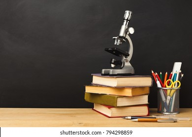 Educational background. Microscope, books pile, pencils and magnifying glass against empty classroom blackboard for copy space. Back to school concept