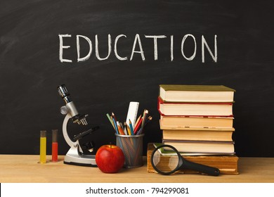 Educational background. Microscope, books pile, pencils, apple, colorful liquids and magnifying glass against classroom blackboard with written word education. Back to school concept
