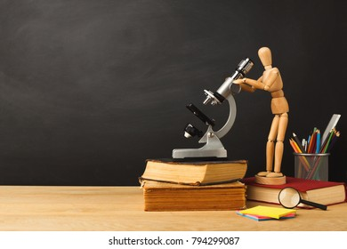 Educational background. Wooden marionette looking in microscope, standing on book against empty classroom blackboard for copy space. Back to school concept