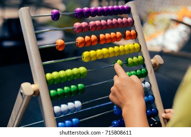 Educational colorful wooden abacus beads on table background. School arithmetic symbol, calculating thinking concept, closeup photography