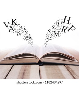 Educational concept. Opened book on wooden table with alphabet letters flying over against white background