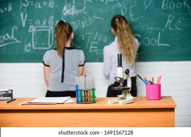 Educational experiment concept. Girls classmates study chemistry. Microscope and test tubes on table. Chemical reactions. Make studying chemistry interesting. Pupil at chalkboard on chemistry lesson.